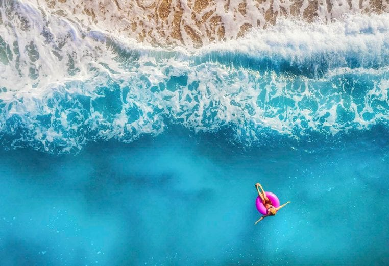 Woman laying on a pink float in the ocean